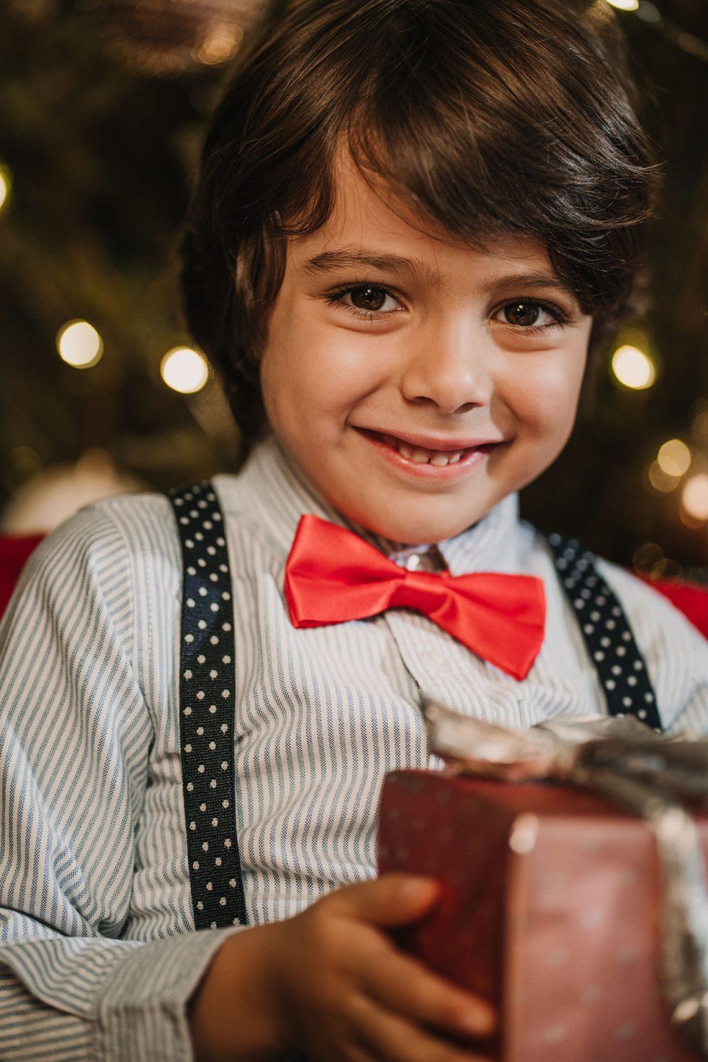 retrato de criança com um presente de natal na mão